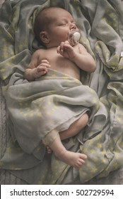 sleeping newborn baby laying on the bed wrapped in the scarf. Sepia Toned
