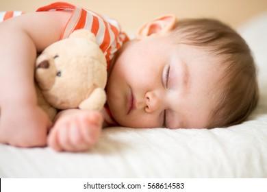 sleeping newborn baby on with a teddy
