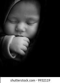 Sleeping newborn baby with thumb in the mouth. Black and white image.