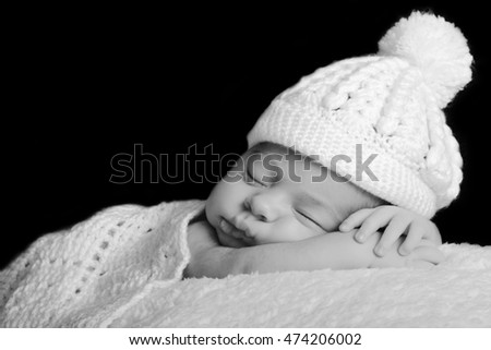 db28a6dfeb6c9 Sleeping newborn baby in a white hat on a white rug. Black background.  Tenderness