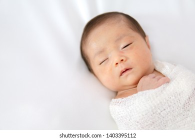 Sleeping newborn baby in white wrap while on white blanket background. Portrait of a infant girl. Cute little newborn child sleeping peacefully.