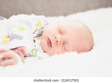 Sleeping Newborn in Comfortable Sleeper Pajamas on a White Soft Blanket