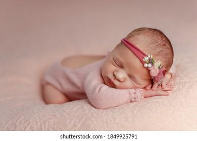 Jeune fille qui dort dans les premiers jours de sa vie sur fond rose