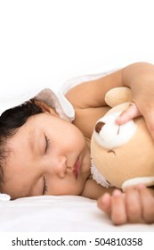 Sleeping newborn girl on bed in bedroom with teddy bear in her arms.