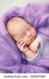 sleeping newborn girl in the purple violet pink wool background, close-up