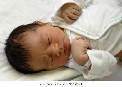 Sleeping newborn in hospital shirt and ID bracelet.