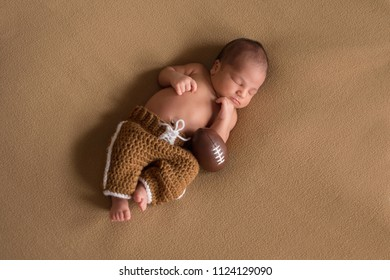 A sleeping, nine day old newborn baby boy wearing crocheted football uniform pants.