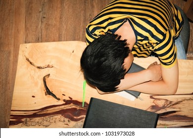 Sleeping on the desk : Top view Children wear a yellow shirt, sleep over a book on a wooden desk.
