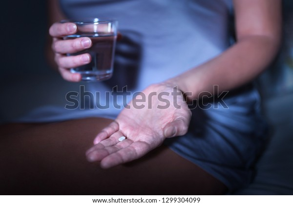 Sleeping pill in hand. Woman sitting on bed with medicine for insomnia or melatonin. Sleepless and tired lady can't fall asleep. Medical pill and tablet for headache or migraine. Addiction to drug.