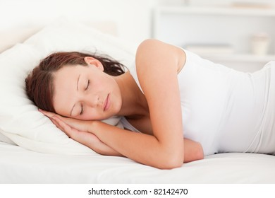 Sleeping red-haired woman in her bedroom