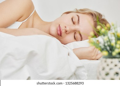 Sleeping smiling beautiful girl on an orthopedic pillow in daylight, white sheets and home interior