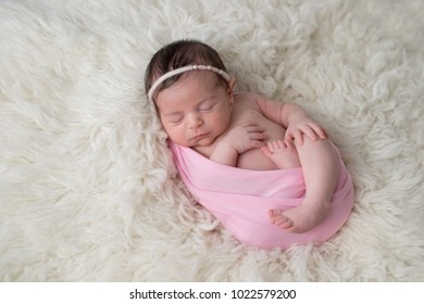 Sleeping, ten day old newborn baby girl swaddled in a light pink wrap. Shot in the studio on a white sheepskin rug.