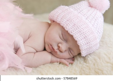 A sleeping three week old baby girl wearing pink hat  with soft focus