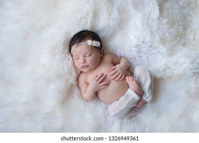 Sleeping, week old newborn baby girl wearing white, knitted pants. Shot in the studio on a white sheepskin rug.