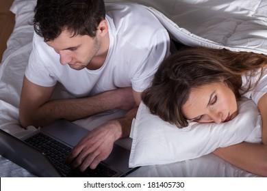 Sleeping wife and her husband using computer
