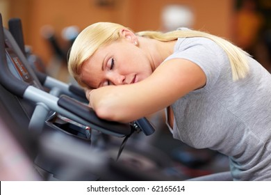 Sleeping woman in gym with her head on a hometrainer