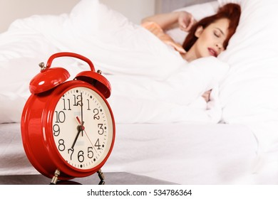 Sleeping woman with her hand touching alarm clock on bed. Relax night morning rest concept.