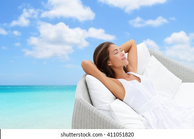 Sleeping woman relaxing lounging on white outdoor sofa day bed lounger on beach ocean background. Asian girl lying down laid back on pillows dreaming or enjoying the sun carefree happy. Home living.