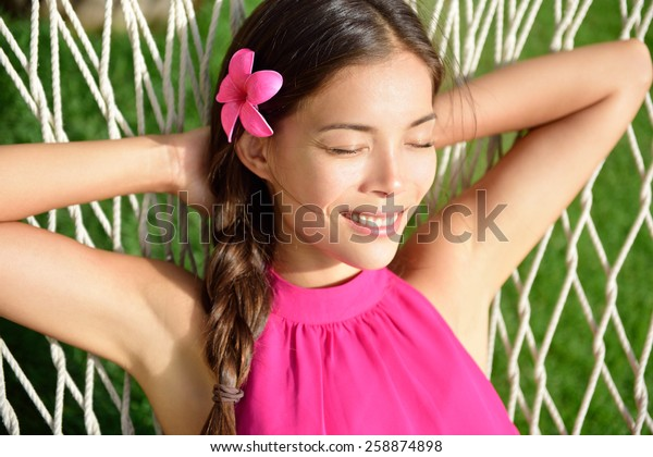 Sleeping woman relaxing on outdoor hammock in the sun tanning and having a nap in home garden or beach resort on summer holidays. Asian young adult portrait wearing pink hair flower and halter top.