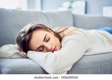 Sleeping woman taking nap on the sofa during the day