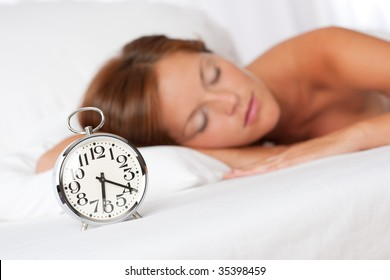 Sleeping woman in white bed with alarm clock