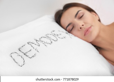 """Sleeping woman and word """"Demodex"""" written with artificial eyelashes on pillow"""