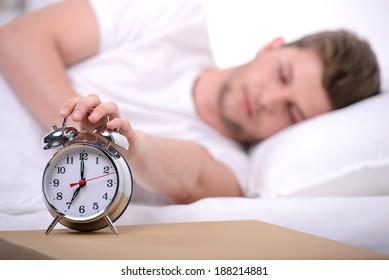 Sleeping. Young man sleeping in bed at home. Alarm ahead