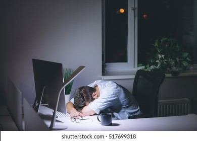 Sleeping young man working on computer at night in dark office. The designer works in the later time. A young man sits at the computer