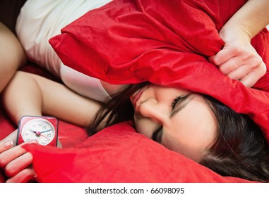 sleeping young woman in bed closes her ears with pillow