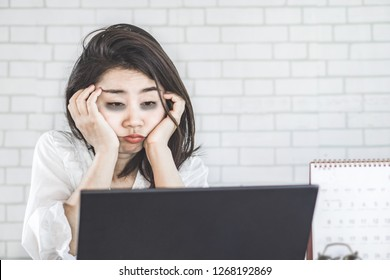 sleepless Asian woman feeling tired and sleepy at workplace eyes looking at computer on desk lazy to work