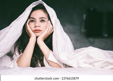 sleepless Asian woman lying down on bed tired from insomnia