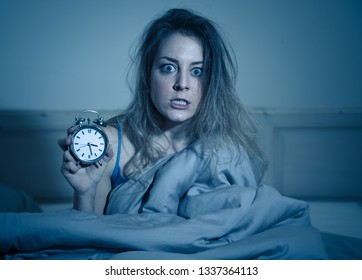 Sleepless and desperate beautiful caucasian woman awake at night not able to sleep, showing clock, feeling frustrated and worried suffering from insomnia in sleep disorder concept.