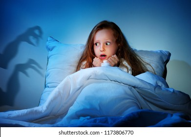 Sleepless girl in her bed having fears of night monsters