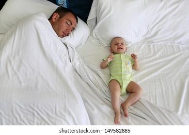 Sleepless parenthood. Father is trying to sleep near awake and crying baby.