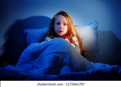 Sleepless scared little girl sitting in her bed