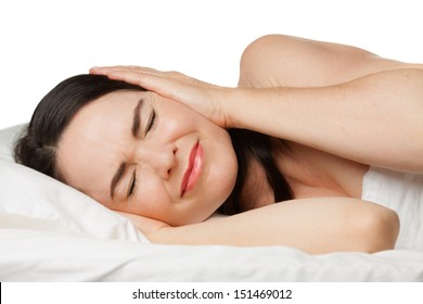 A sleepless woman lying in bed covering her ears. Isolated on white.