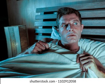 sleepless young man lying in bed stressed and scared suffering nightmare and horror bad dream grabbing duvet frightened and paranoid in sleeping disorder and resting problem lifestyle concept