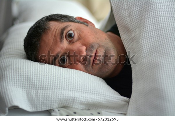Sleeplessness man suffering from Insomnia sleep disorder. Real people. Copy space.