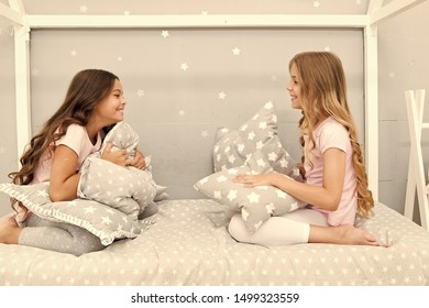 Sleepover party ideas. Girls happy best friends or siblings in cute stylish pajamas with pillows sleepover party. Sisters play pillows bedroom party. Pillow fight pajama party. Evening time for fun.