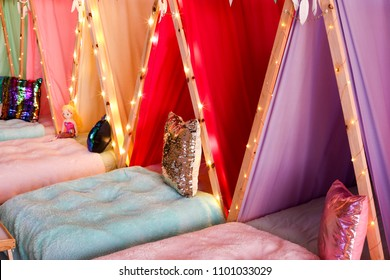 A sleepover party with lots of colourful teepees and fairy lights.
