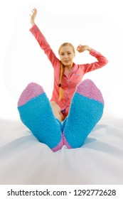 Sleepwear fashion and accessories concept. Woman in pajamas wearing furry warm socks relaxing on bed, feet closeup.