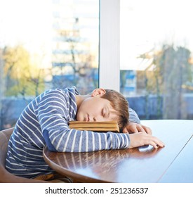 Sleepy 12 years old children boy sitting at the wooden desk and sleeping over the book, composition against the window