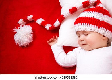 Sleepy baby on red blanket in knitted hat