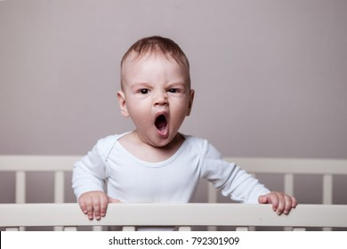 sleepy baby stands on the side of the cot, yawns, wants to sleep