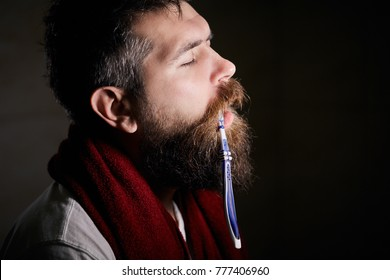 sleepy bearded man brushing teeth with a toothbrush in front of the bathroom mirror in morning. man sleeps with toothbrush in the mouth, heavy morning. how to wake up in the morning to go work?
