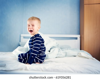 Sleepy boy sitting in bed and crying. Tired child in bedroom