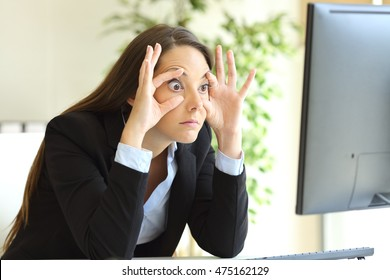 Sleepy businesswoman trying to stay awake keeping the eyes opened with the fingers watching a desktop computer monitor at office