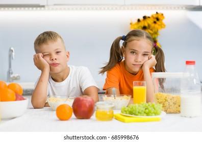 Sleepy children eat breakfast in the morning