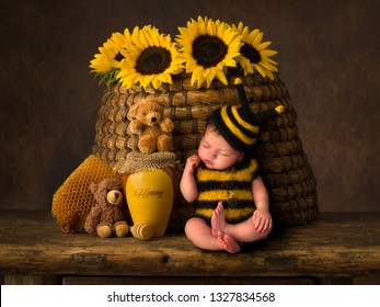 Sleepy cute baby in bee outfit resting against an antique beehive