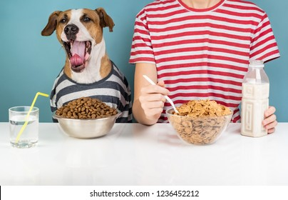 Sleepy dog and human having breakfast together. Minimalistic illustrative concept of yawning dog with a person in front of pet food and cereals bowls